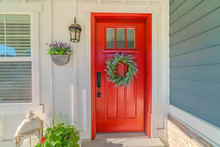 Red Front Door Of Modern Home With Green Wreath