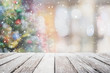canvas print picture - Empty wood table top on blur with bokeh Christmas tree and new's year decoration on window background with snowfall - can be used for display or montage your products.