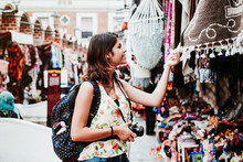 Latin Woman Backpacker Shopping In A Tourist Market In Mexico City, Mexican Traveler In America