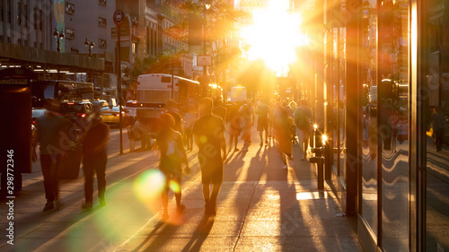Fototapeta Sunlight shines on the diverse crowds of people walking down the busy sidewalk on 34th Street through Midtown Manhattan in New York City obraz