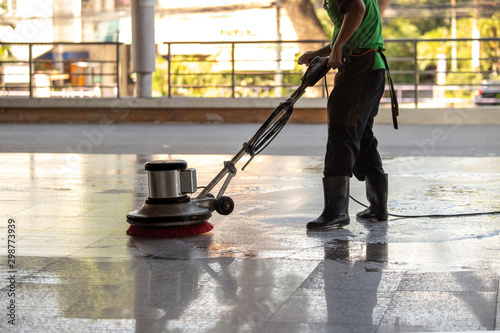 Obraz na plátně The worker cleaning floor exterior walkway using polishing machine and chemical