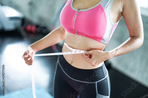 Carta da parati  Women in pink sportswear are measuring around the waist.
