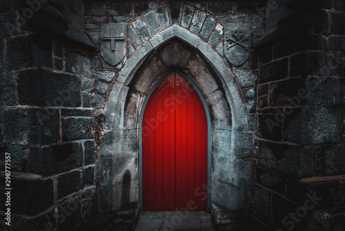 Fotomural  Scary pointy red wooden door in an old and wet stone wall building with cross, skull and bones at both sides