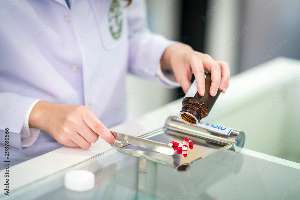 Fototapety, obrazy: Pharmacist separate and count medicine capsule in steel tray by hand