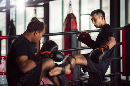 Fotografía Asian kickboxing player and him trainer in boxing gym