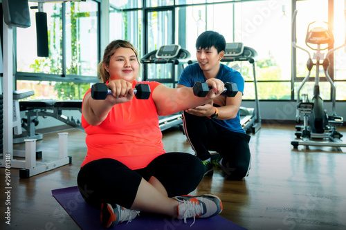 Obraz Asian fat girl work out and weight lifting with her trainer - fototapety do salonu