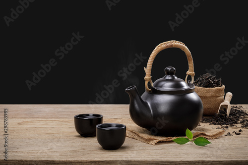 Recess Fitting Tea Cup of hot tea with teapot, green tea leaves and dried herbs on the wooden table isolate black background with empty space, Organic product from the nature for healthy with traditional