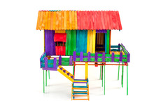 The House Is Made Of Toys From Colorful Popsicle Sticks Isolated On A White Background.