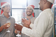 Cheerful multi-ethnic business people discussing funny stories and drinking sparkling wine at Christmas party in office