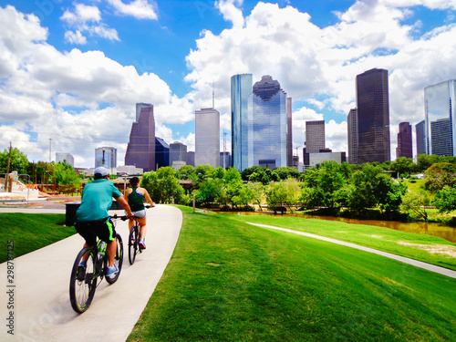 Montage in der Fensternische Texas Riding Bikes on Paved Trail in Houston Park (view of river and skyline of downtown Houston) - Houston, Texas, USA