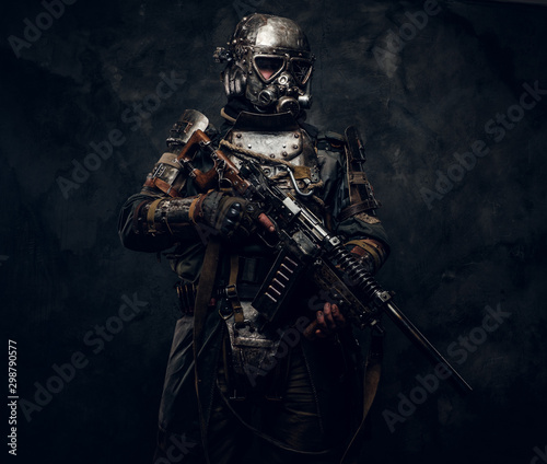 Concept of post - apocalypse futuristic warrior with weapon in hands at dark photo studio Fototapete