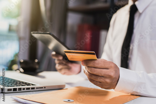 Male businessman use credit cards to conduct financial transactions through phones, tablet, and laptop Fototapete