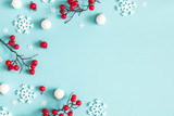 Christmas or winter composition. Snowflakes and red berries on blue background. Christmas, winter, new year concept. Flat lay, top view, copy space