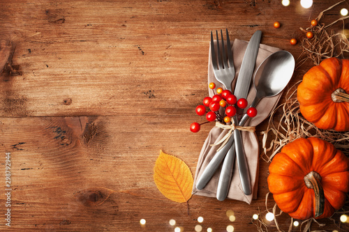 Serving for Thanksgiving dinner with napkin, cutlery and pumpkins top view. Autumn table setting. - 298792944