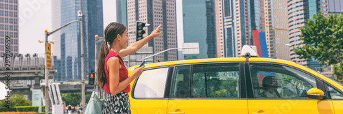 Fotografia Taxi cab mobile phone app Asian business woman walking on street hailing a car for a ride using smartphone panoramic banner