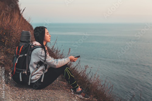 Foto auf Leinwand Dunkelbraun The concept of Hiking and sports recreation. A woman with a backpack behind her sits on a rock, listening to music with headphones and holding a phone. In the background, the sea. Copy space