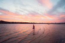 Beautiful Colourful Sunset At Point Walter, Woman In Summer Dress Walking Through The Water On The Sand Bank With Swans And Perth City In The Background.