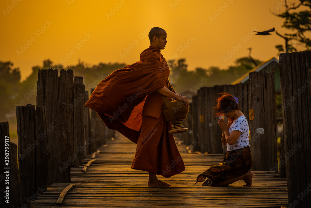 Fototapety, obrazy: Asian buddha religion lady giving food to monk in early morning  to pay respect to Buddha is do good things for Buddhist at U-bein bridge , Myanmar.
