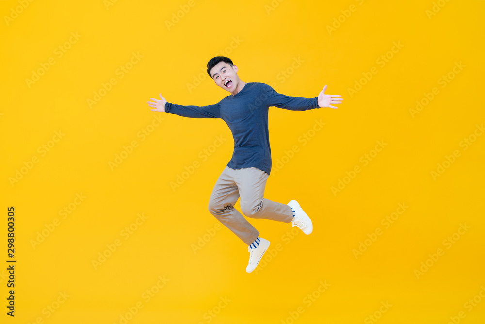 Fototapety, obrazy: Asian man smiling and jumping with arms outstretched
