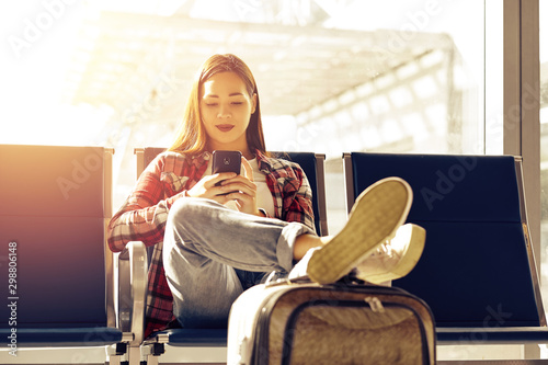 Obraz na plátně  Air travel concept with young casual girl sitting with hand luggage suitcase