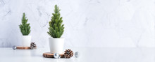 Christmas Tree With Pine Cone,decor Xmas Ball On Wood Log At White Table And Marble Tile Wall Background.clean Minimal Simple Style.holiday Still Life With Space To Adding Text