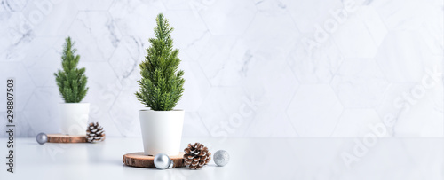 christmas tree with pine cone,decor xmas ball on wood log at white table and marble tile wall background.clean minimal simple style.holiday still life with space to adding text - 298807503