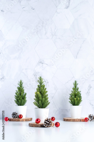Three christmas tree with pine cone and decor xmas ball on white table and marble tile wall background.clean minimal simple style.holiday still life mockup banner with space to adding text