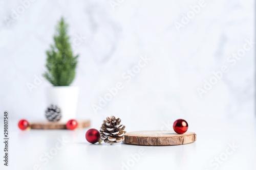 christmas tree with pine cone and decor xmas ball and empty wood log plate on white table and marble tile wall background.clean minimal simple style.holiday still life mockup to display design - 298807549