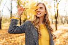 Happy Young Girl Smiling With Autumn Yellow Leaf In Park
