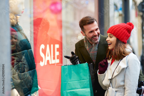 Happy couple looking at shop window with clothing Wallpaper Mural
