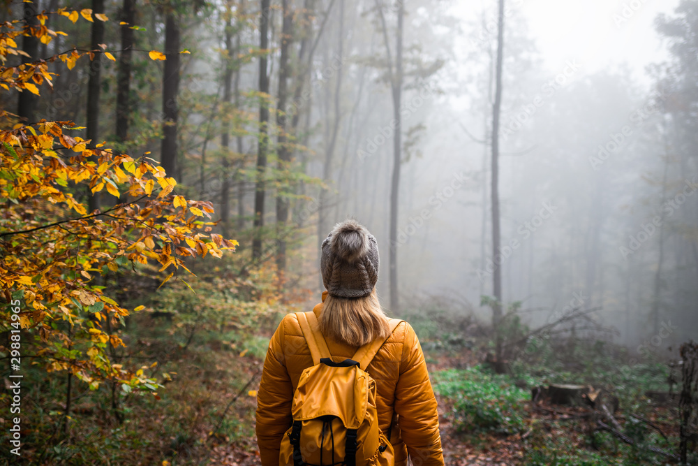 Fototapety, obrazy: Woman with knit hat and backpack hiking in foggy woodland