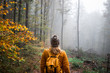 Woman with knit hat and backpack hiking in foggy woodland