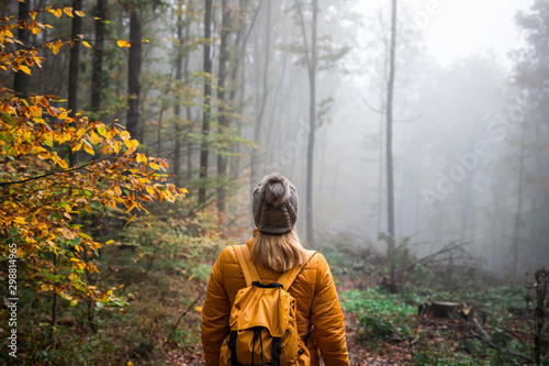 Woman with knit hat and backpack hiking in foggy woodland Billede på lærred