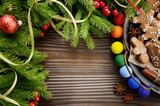 Fototapeta Rainbow - Flat lay Christmas background of spruce branches and tray with gingerbread man cookies on wooden table