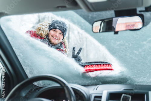 cleaning car after snow storm smiling man with brush - 298815772