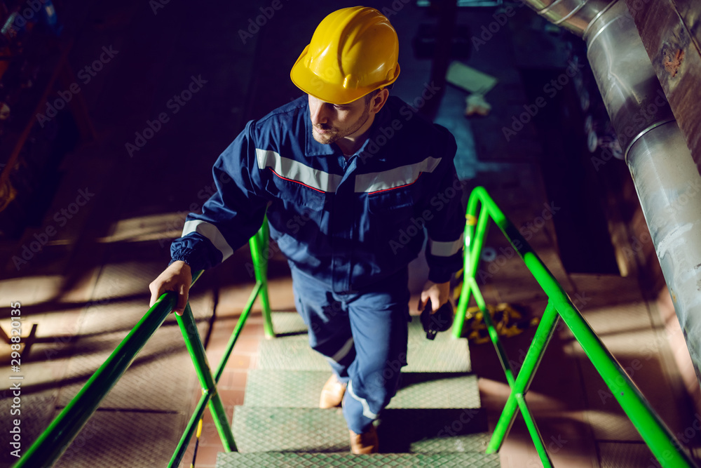 Fototapety, obrazy: Full length of caucasian worker dressed in blue work suit and with protective helmet on head climbing up the stairs. Energy plant interior.