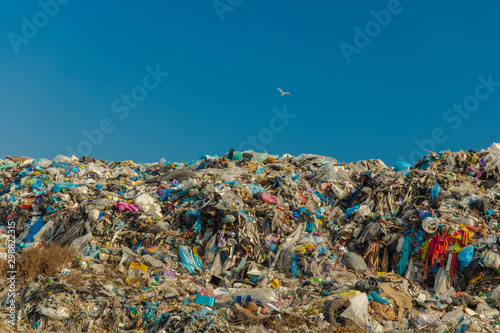 Fototapeta garbage dump huge polluted hill on blue sky background with flying bird, empty c