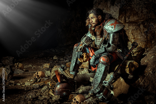 Powerful knight in the armor with the hammer is sitting on the stone Fototapete