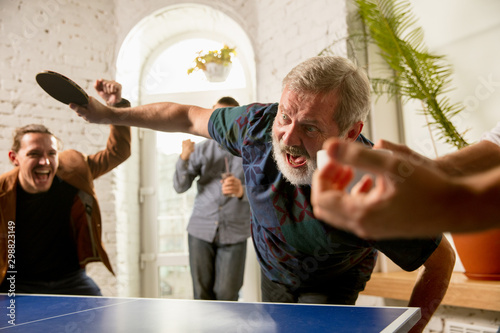 Fotomural  Young people playing table tennis in workplace, having fun