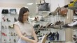 Thigh-up shot of stylish young Chinese woman with short hair, in glasses, standing in footwear shop next to full shelves and checking out white shoe with stiletto heel