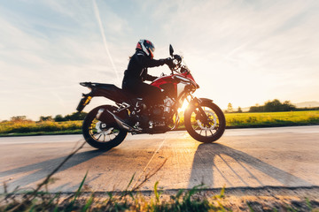 Fast motorcycle drive on asphalt road at sunset.