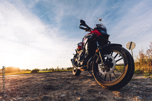 Fotomural  Adventure motorbike on roadside at sunset. Offroad trip.