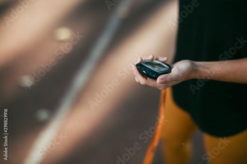 Close up of female hand holding stopwatch. Fototapeta