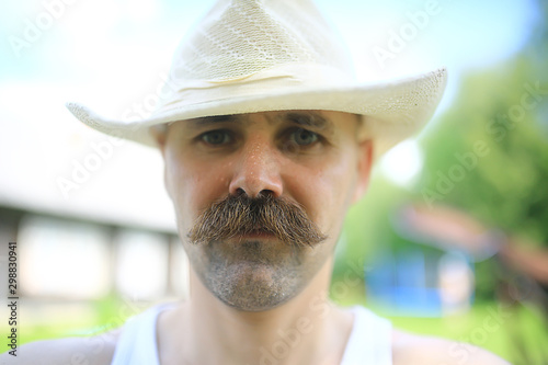 Valokuva  mustachioed young farmer, portrait of a man with a big mustache in a hat