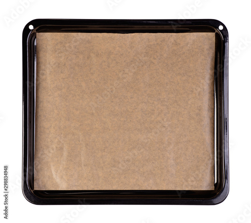 Photo Baking tray with brown baking paper isolated on white background