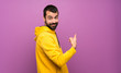 canvas print picture - Handsome man with yellow sweatshirt pointing back