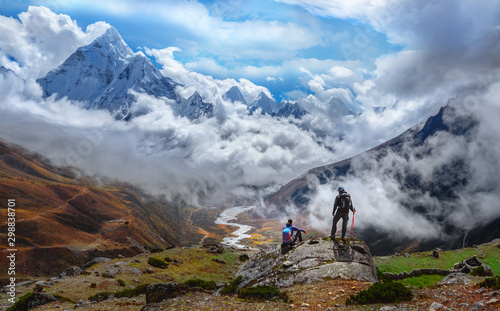 Active hikers hiking, enjoying the view, looking at Himalaya mountains landscape Wallpaper Mural