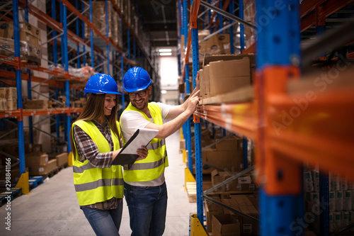 Positive cheerful warehouse workers checking inventory on shelves together and controlling distribution of products in large storage area Wallpaper Mural