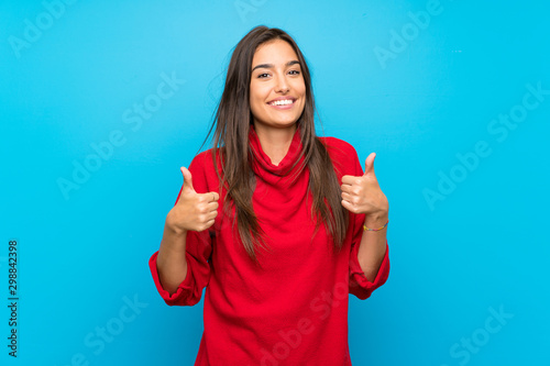 Obraz Young woman with red sweater over isolated blue background giving a thumbs up gesture - fototapety do salonu