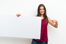 Young Woman Over Isolated White Background Holding An Empty White Placard For Insert A Concept